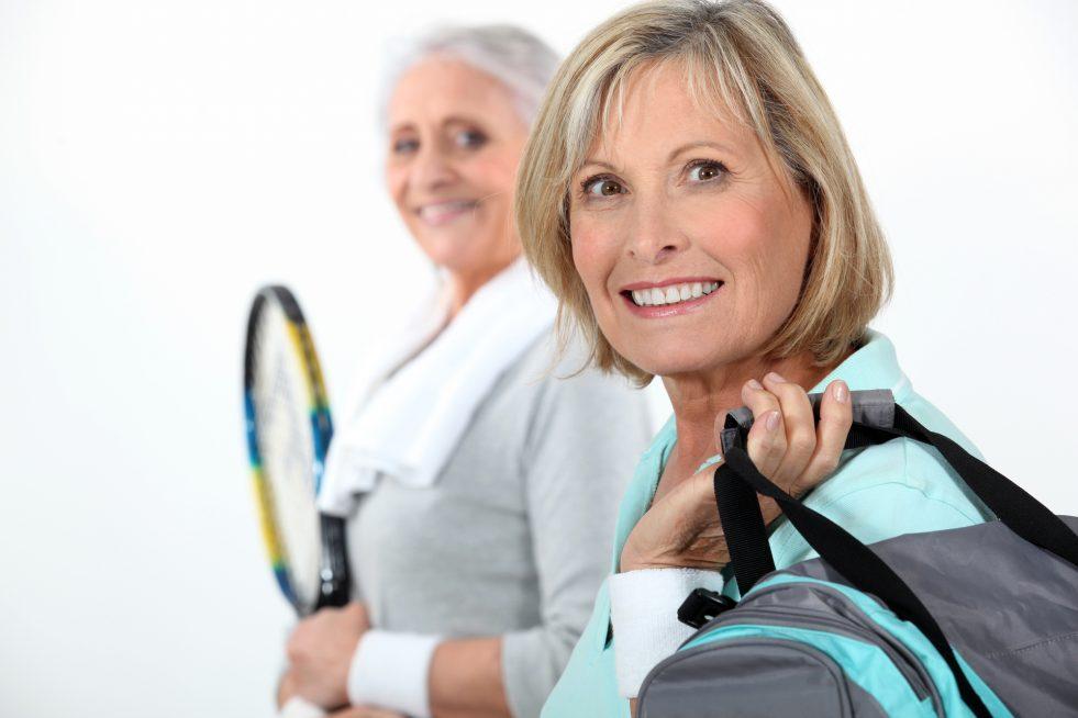 Two mature women playing tennis.