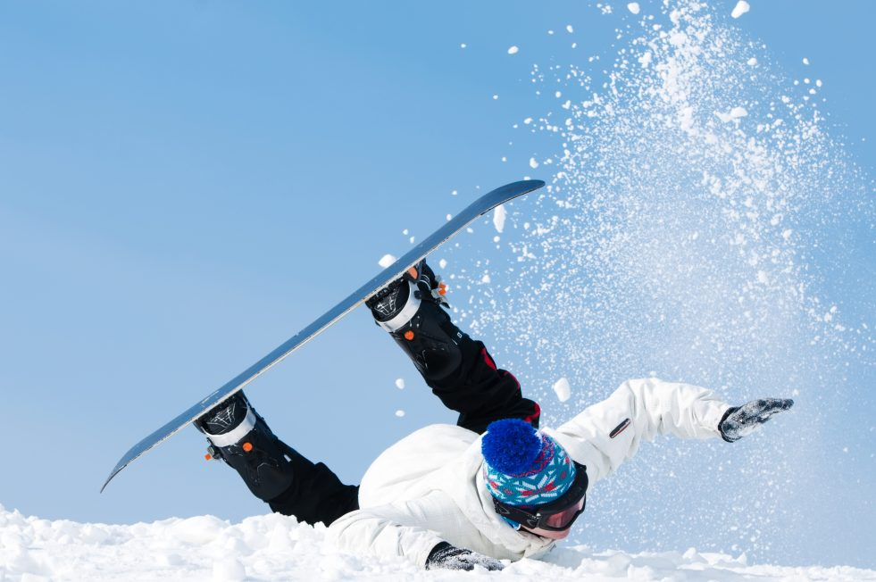 falling young man on snowboard at snowy winter.