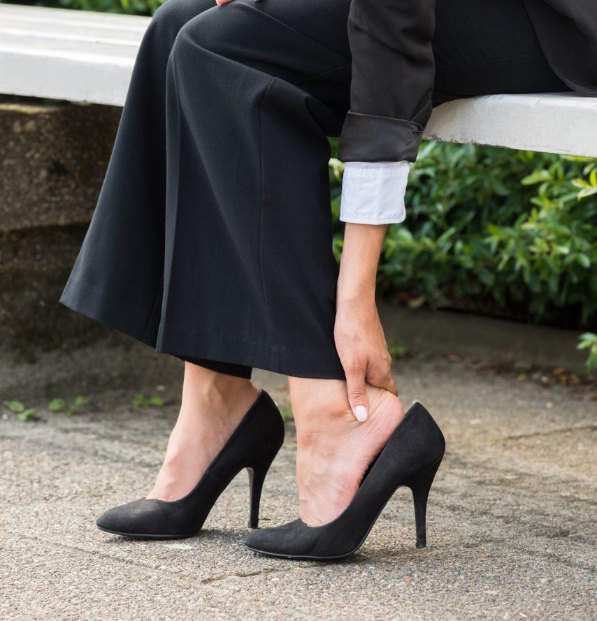 Woman in black high heels massaging heel of foot.