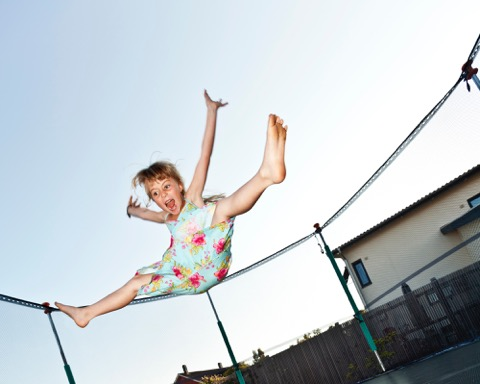Girl jumping on trampoline.