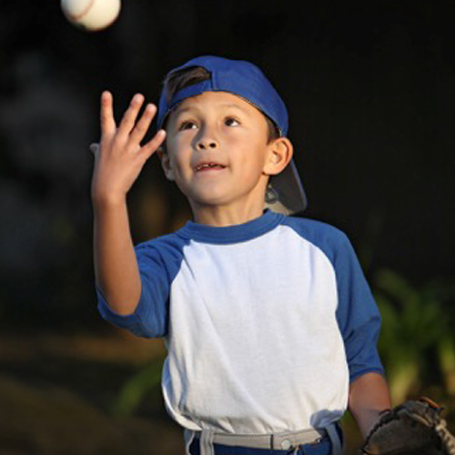 little boy catching baseball.