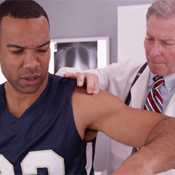 A doctor examining a man's shoulder.