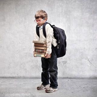 Photo of a small child holding a pile of books.