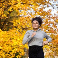 Woman jogging with yellow fall leaves in the background.
