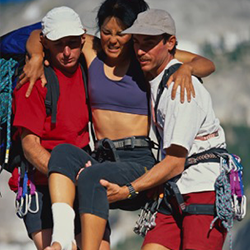 Two men carrying an injured woman wincing in pain.