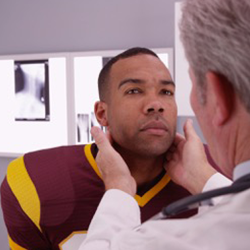 Photo of a doctor examining a man's neck.