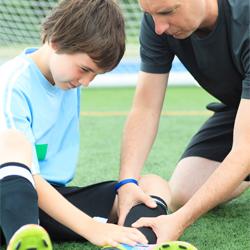 A coach helping an injured soccer player.