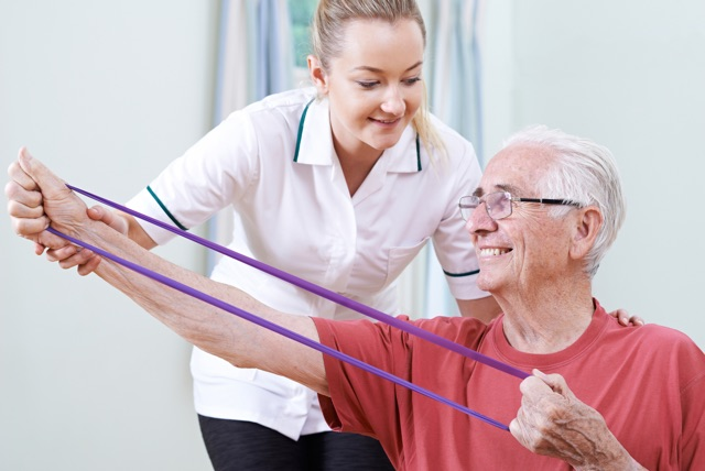 Female PT helping an older man with an exercise band.