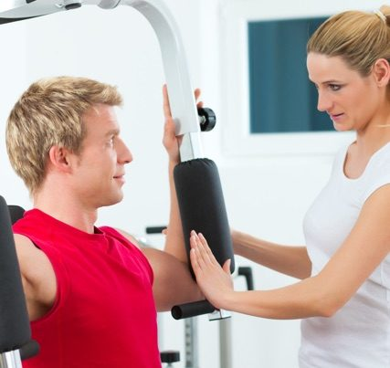 woman helping man use a piece of workout equipment.