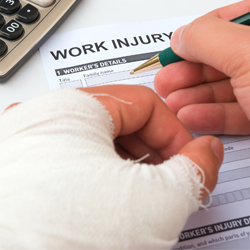 Man with injured hand filling out worker's comp paperwork.