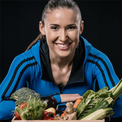 female athlete smiling behind a pile of vegetables.