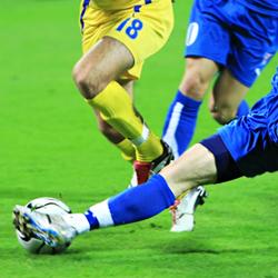 closeup of legs kicking a soccer ball.