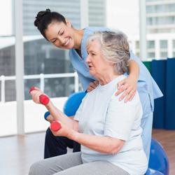 A female physical therapist helping elderly woman lift weights.