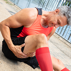 man holding his hamstring wincing in pain.
