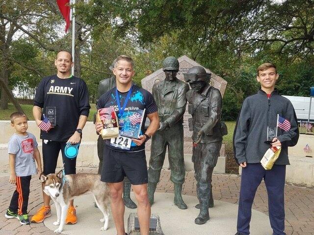 Dan standing holding awards near veteran statues.