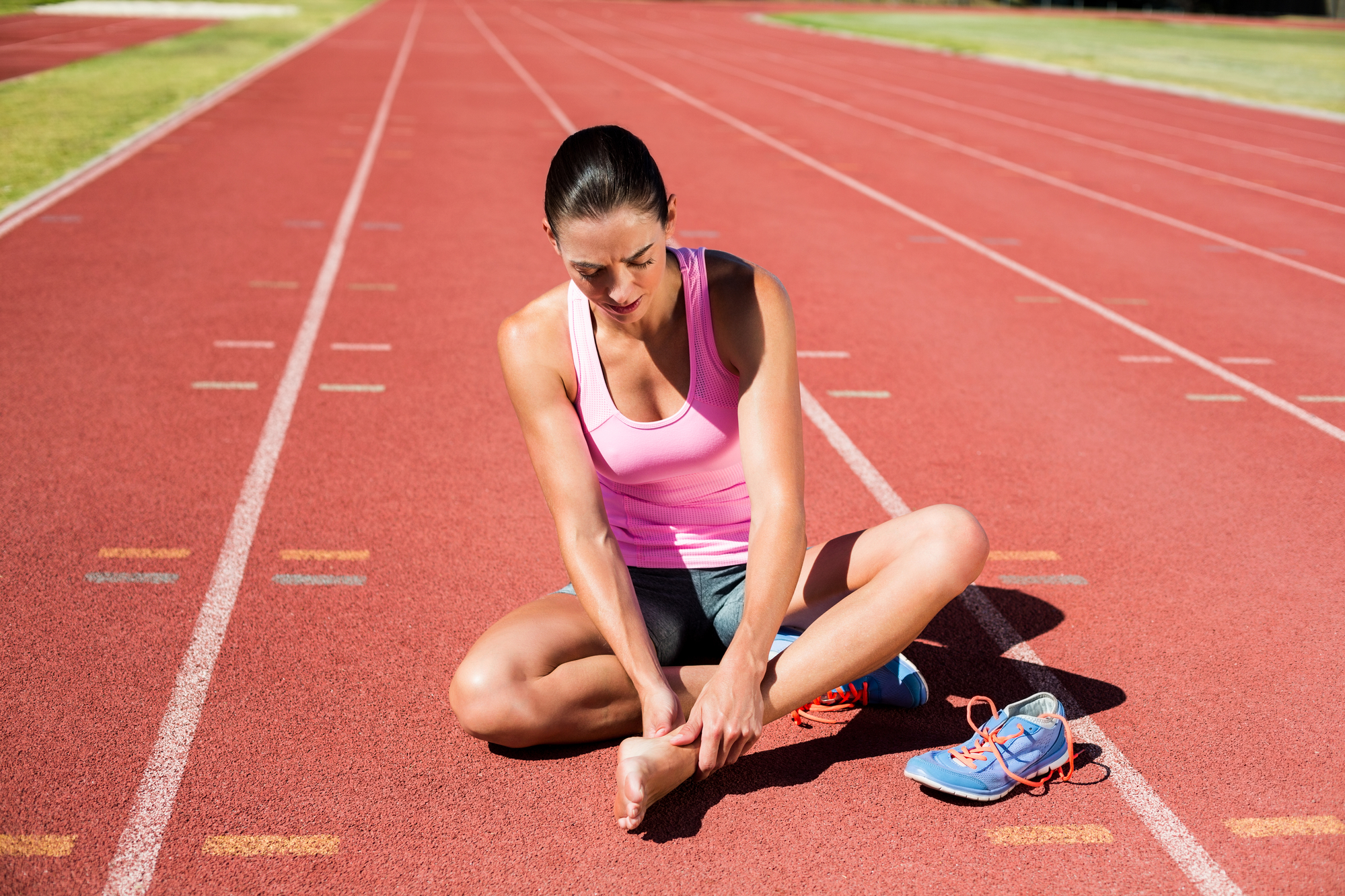 Female athlete with foot pain on running track on a sunny day.