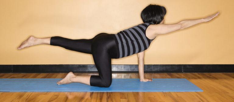 woman doing a bird dog stretch.