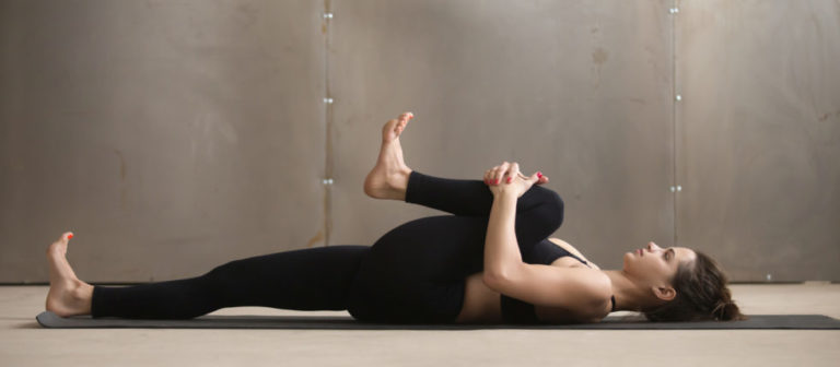 woman doing a knee to chest stretch.