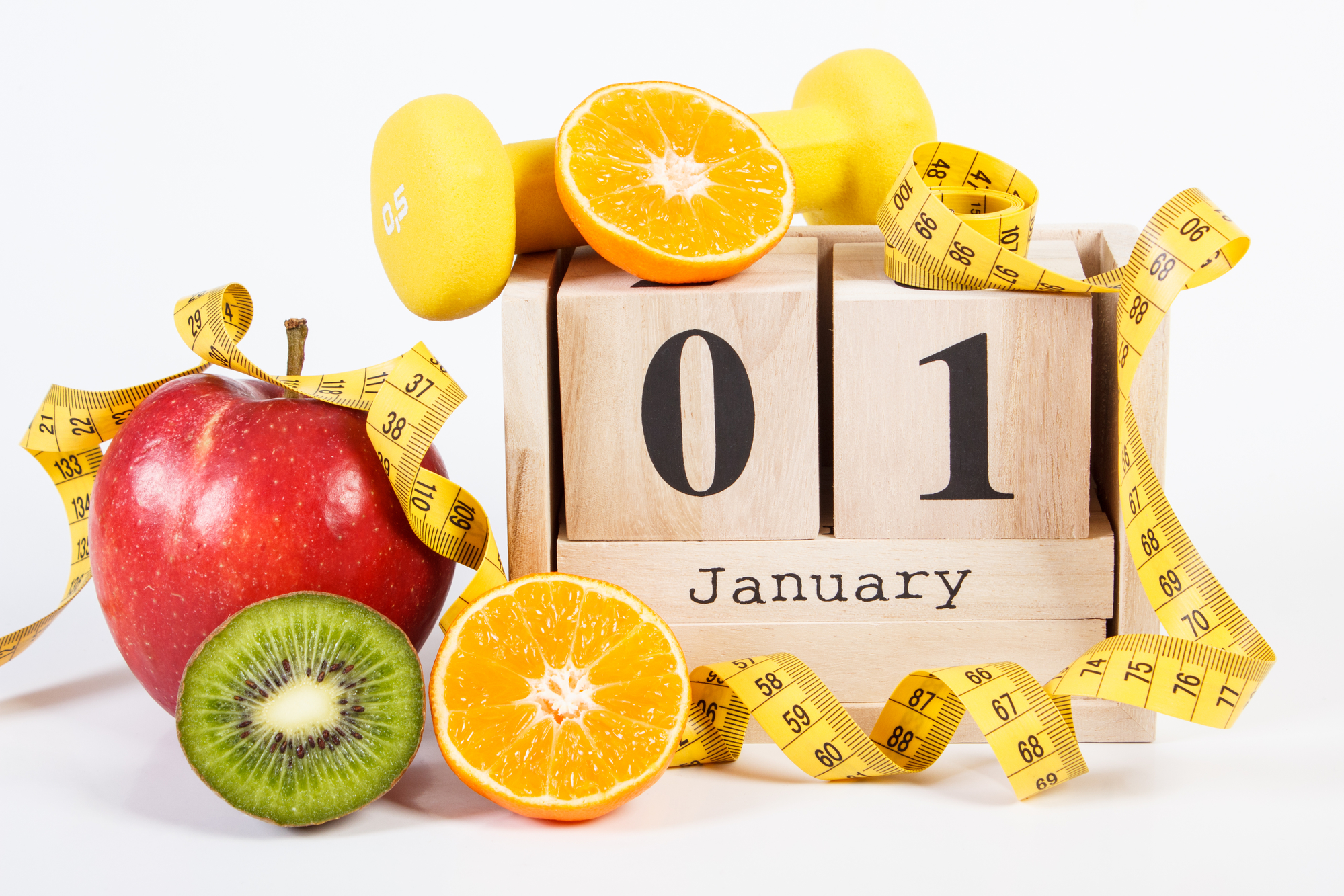 January 1 on cube calendar, fresh fruits, dumbbells and tape measure, new years resolutions of healthy lifestyle.