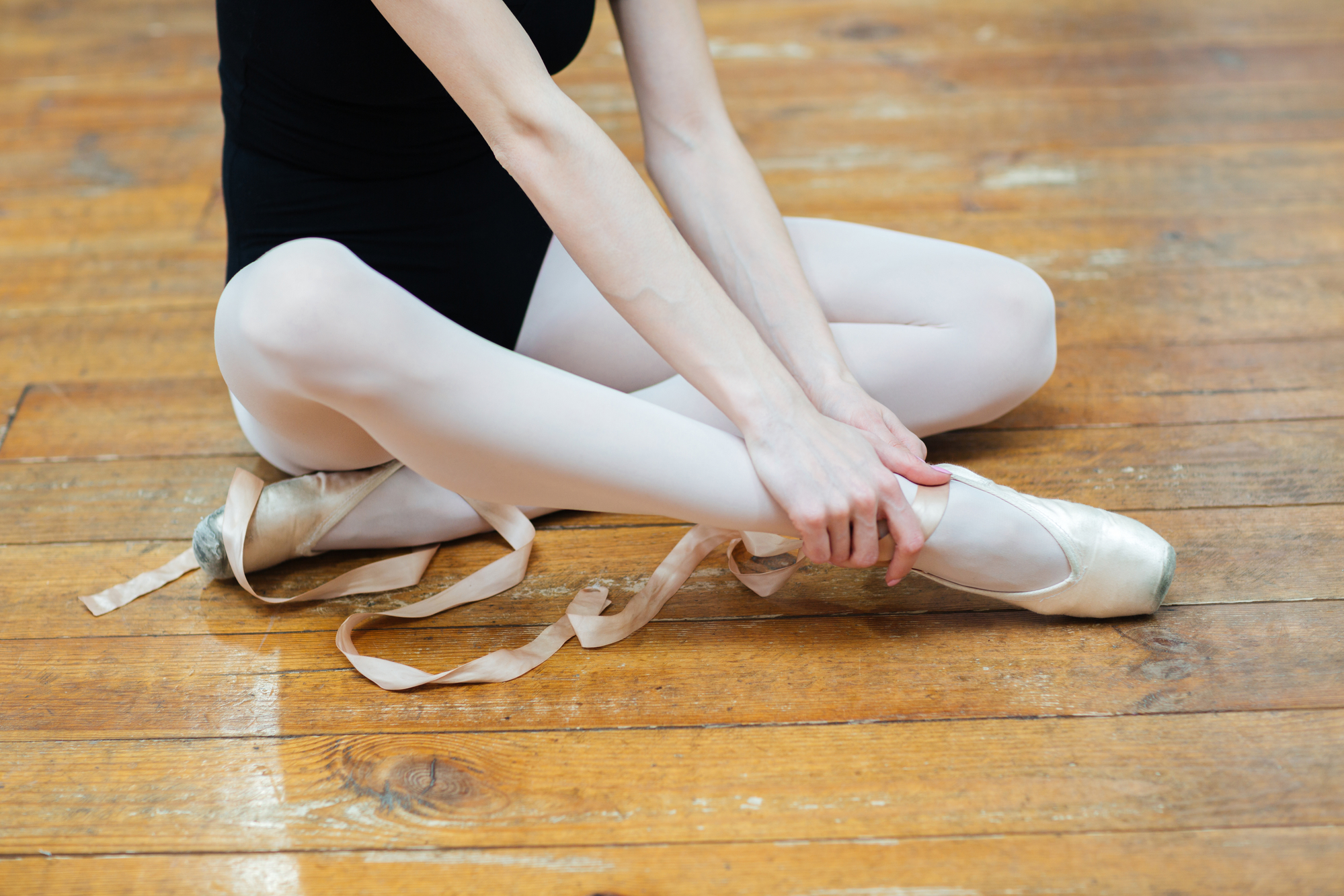 Cropped image of a ballerina in pointes having pain in ankle.