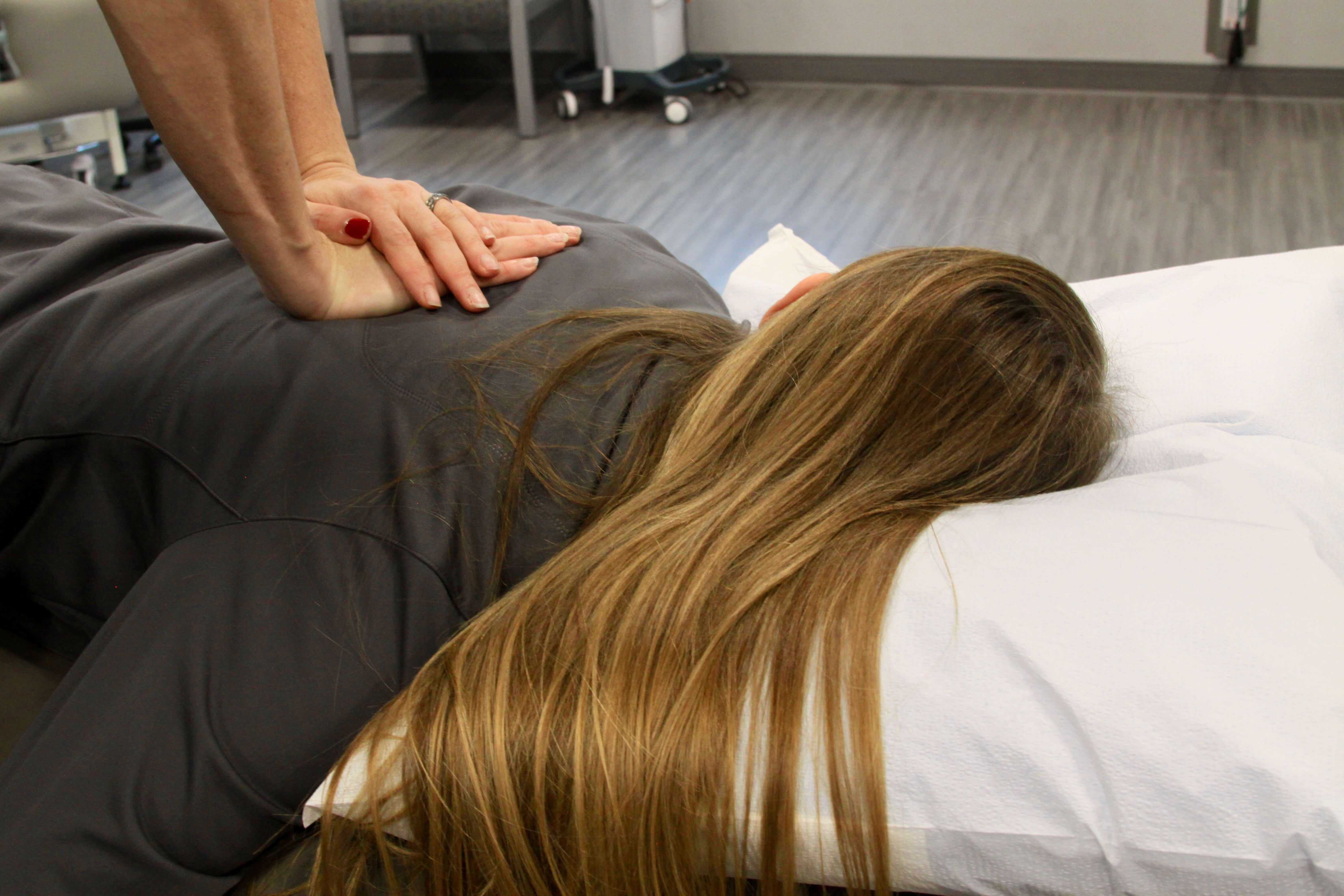 Woman laying on stomach while physical therapist works on her back.
