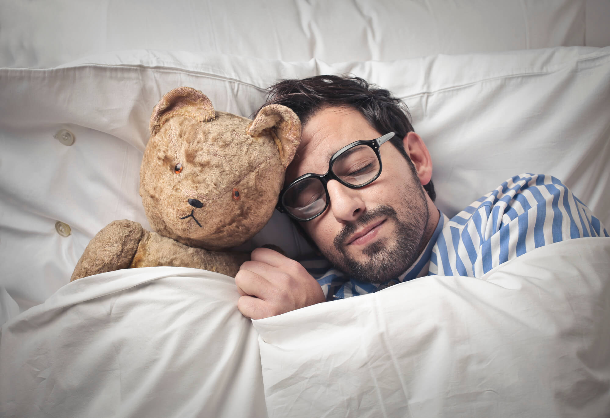 Adult man snuggling teddy bear, sleeping in bed.