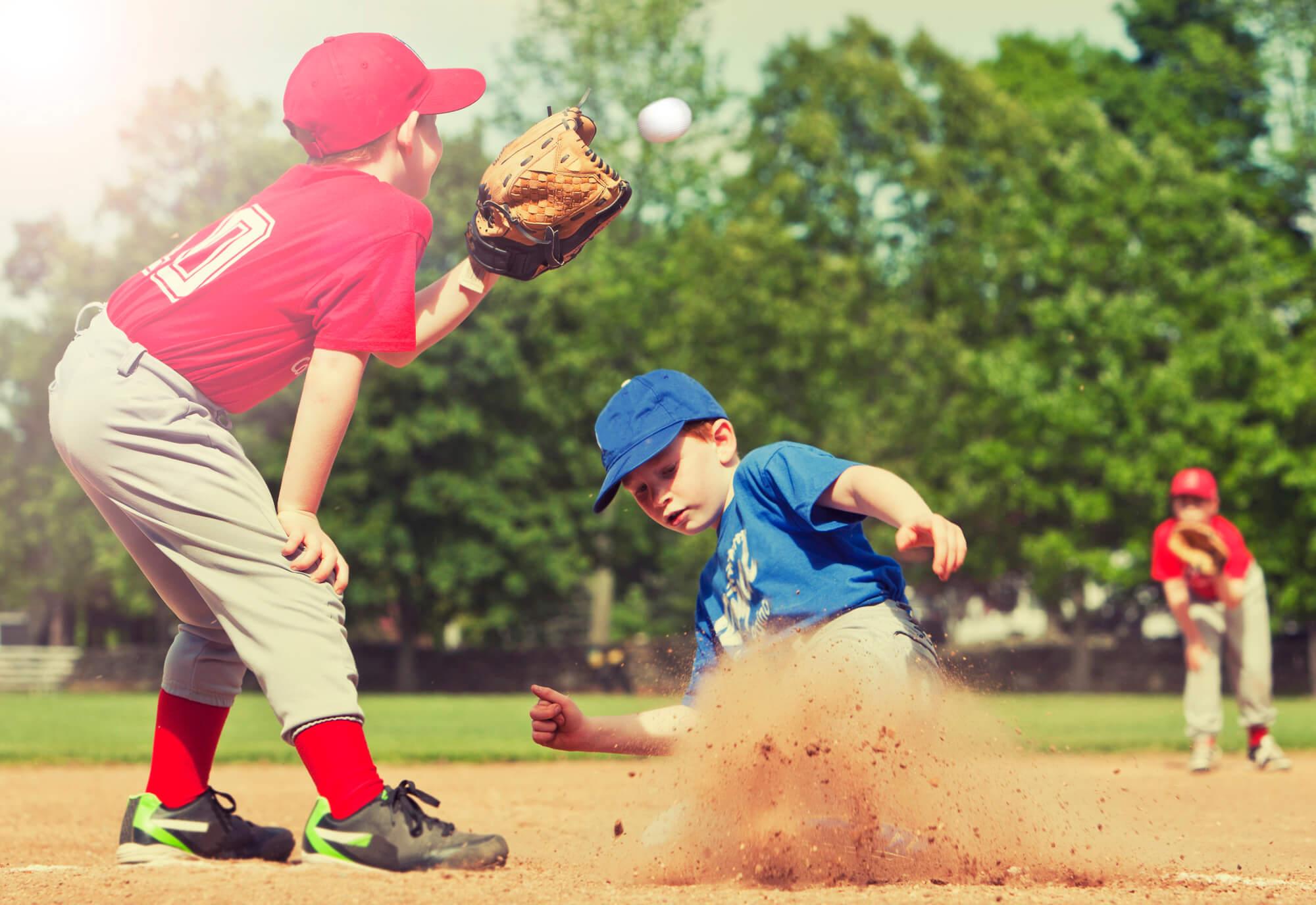 Little league baseball player sliding into second base.