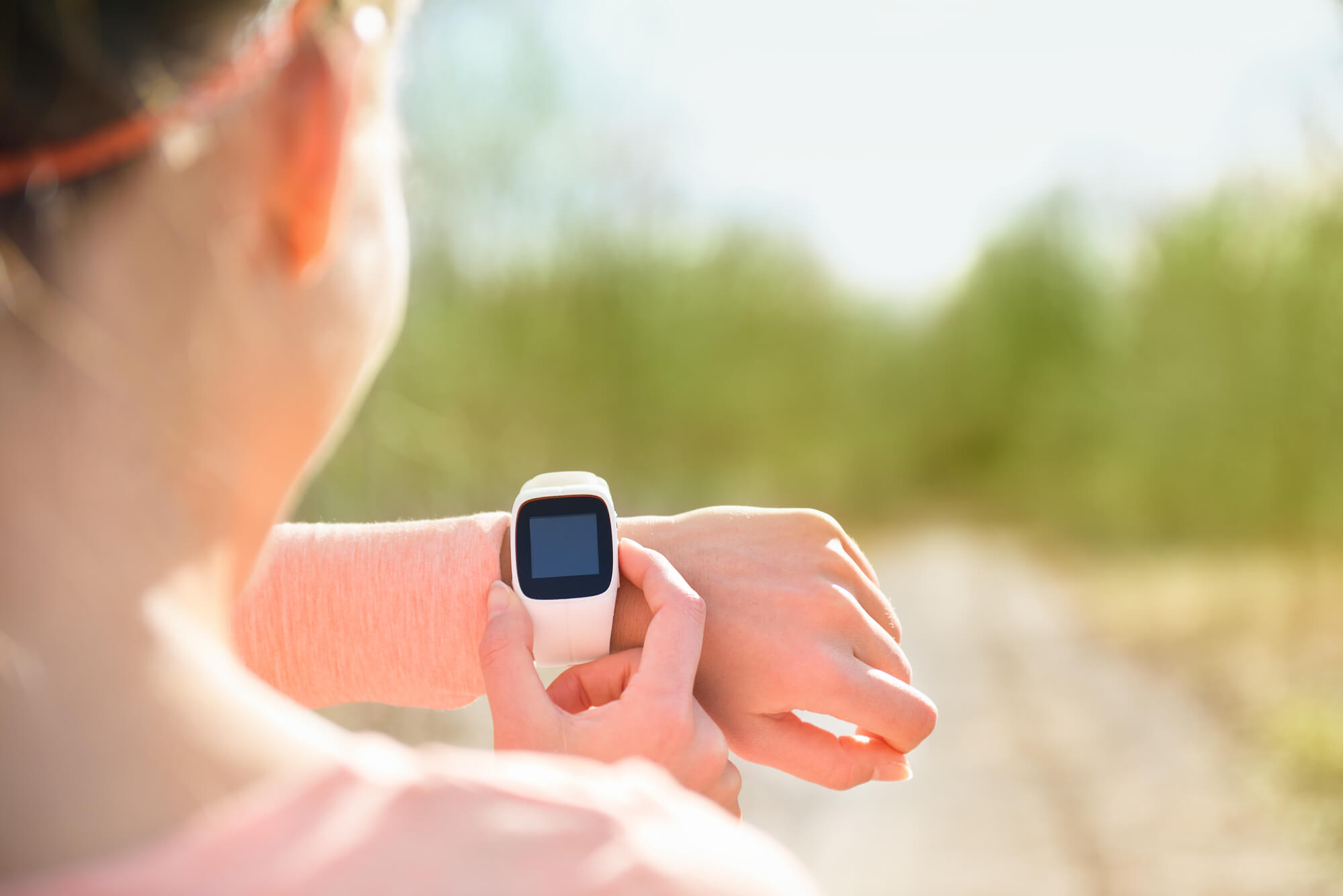 Female runner looks at wearable technology.