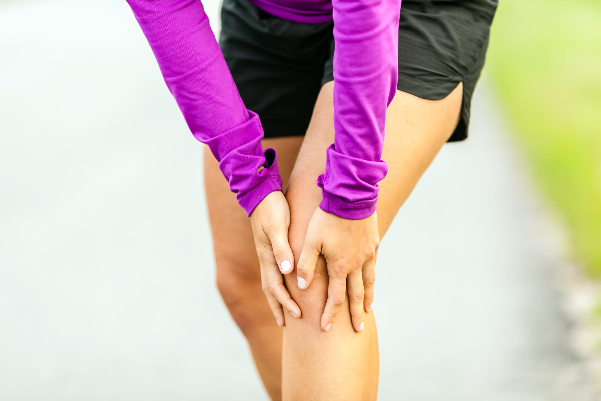 Female runner holding sore knee.