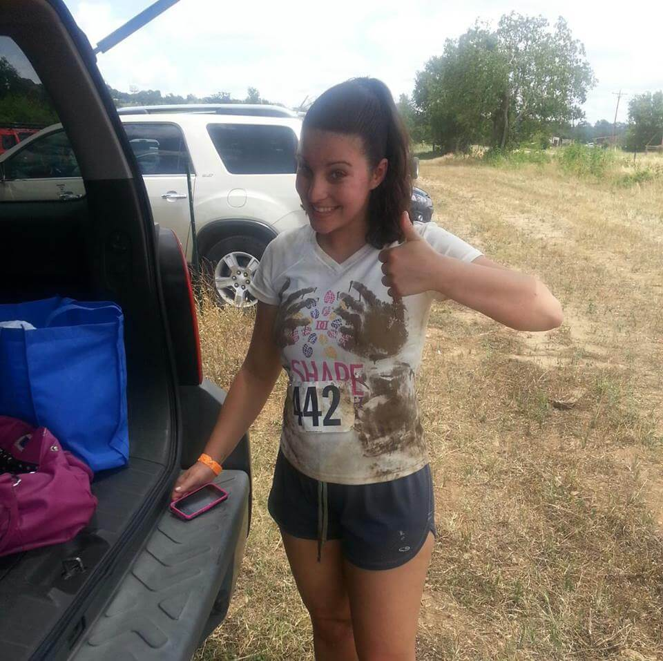 Myranda smiles and gives a thumbs up after participating in a mud run.