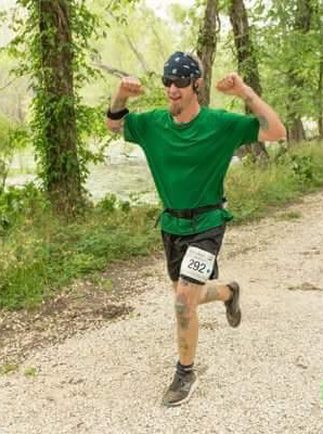 Action shot of Noah flexing for the camera while participating in a race on a trail outside.