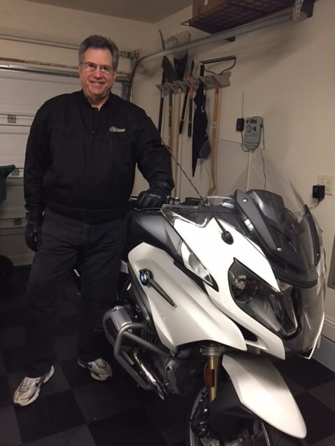 Tom Evan standing next to a motorcycle in a garage.