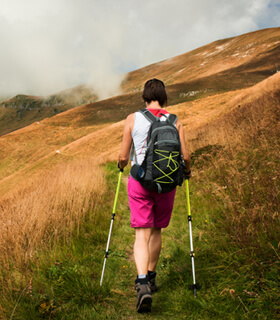 Woman backpacking along a treeless hillside with walking stick.