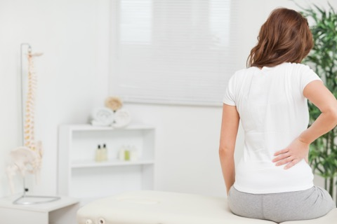 Woman holding her lower back while sitting on a bed.