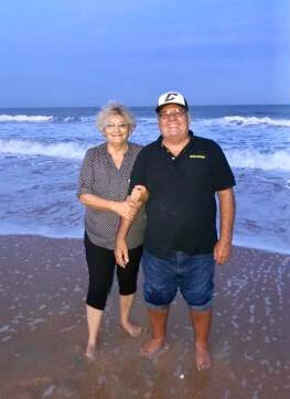Susan and her partner standing on the beach.