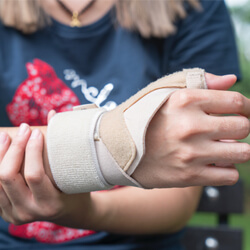 Close up shot of woman holding her wrist in a splint.