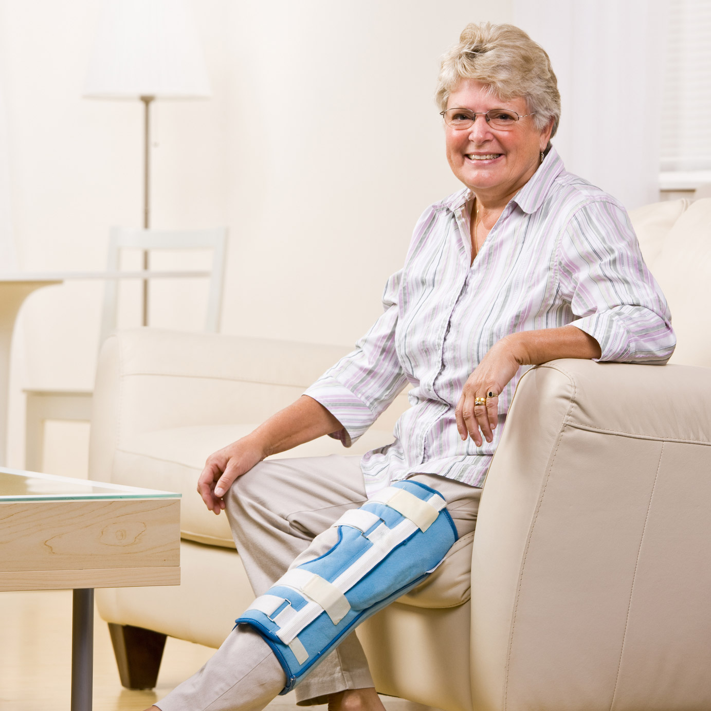 Older woman wearing knee brace after knee replacement surgery.
