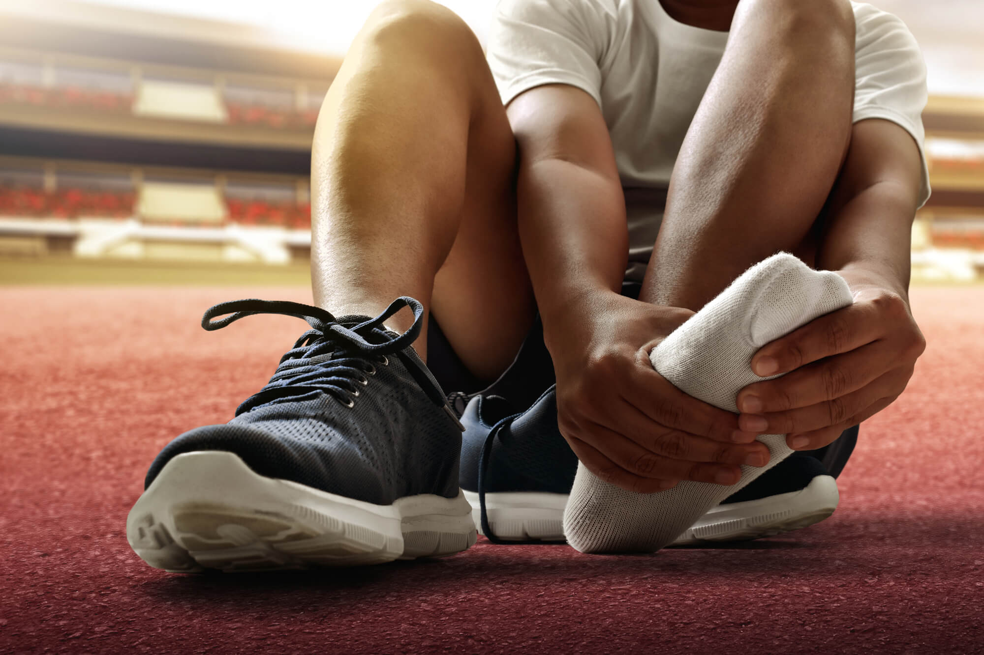 Runner examining painful area in his foot.