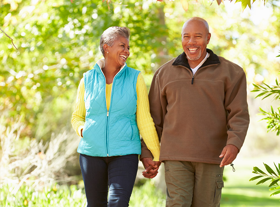 Older couple smiling, walking through the park.