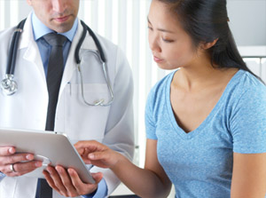 Doctor looking at tablet with female patient.