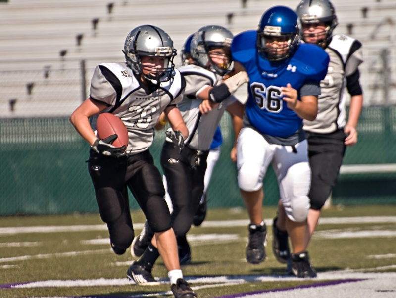 Young football players running during game.