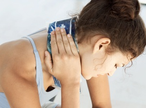 A woman tilts her neck and holds an ice pack to ease neck pain