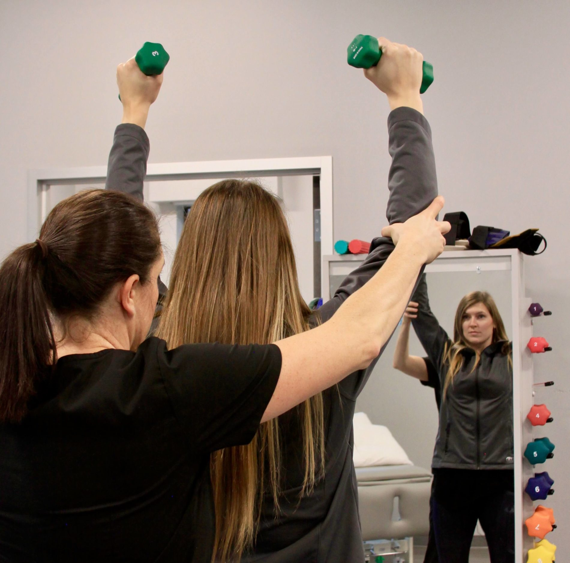 Physical therapist assisting young woman with weights during therapy.