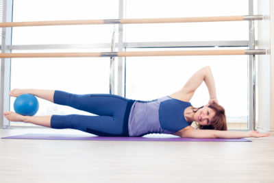 Woman practicing Pilates exercise.