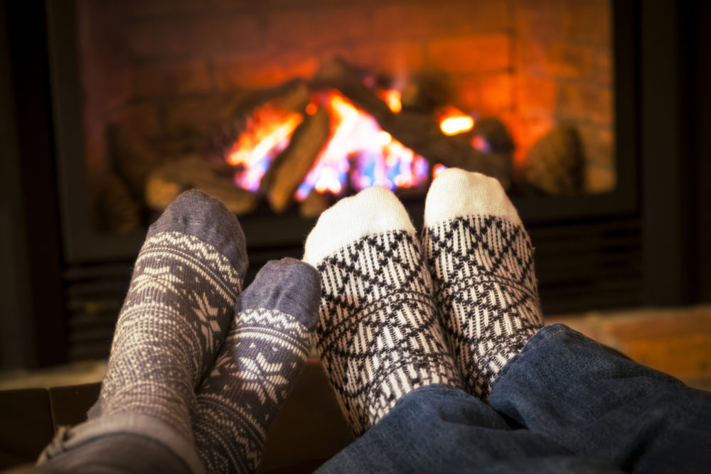 Feet in cozy winter socks warming by a fireplace.