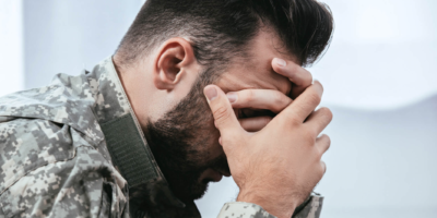 Depressed man in army uniform.