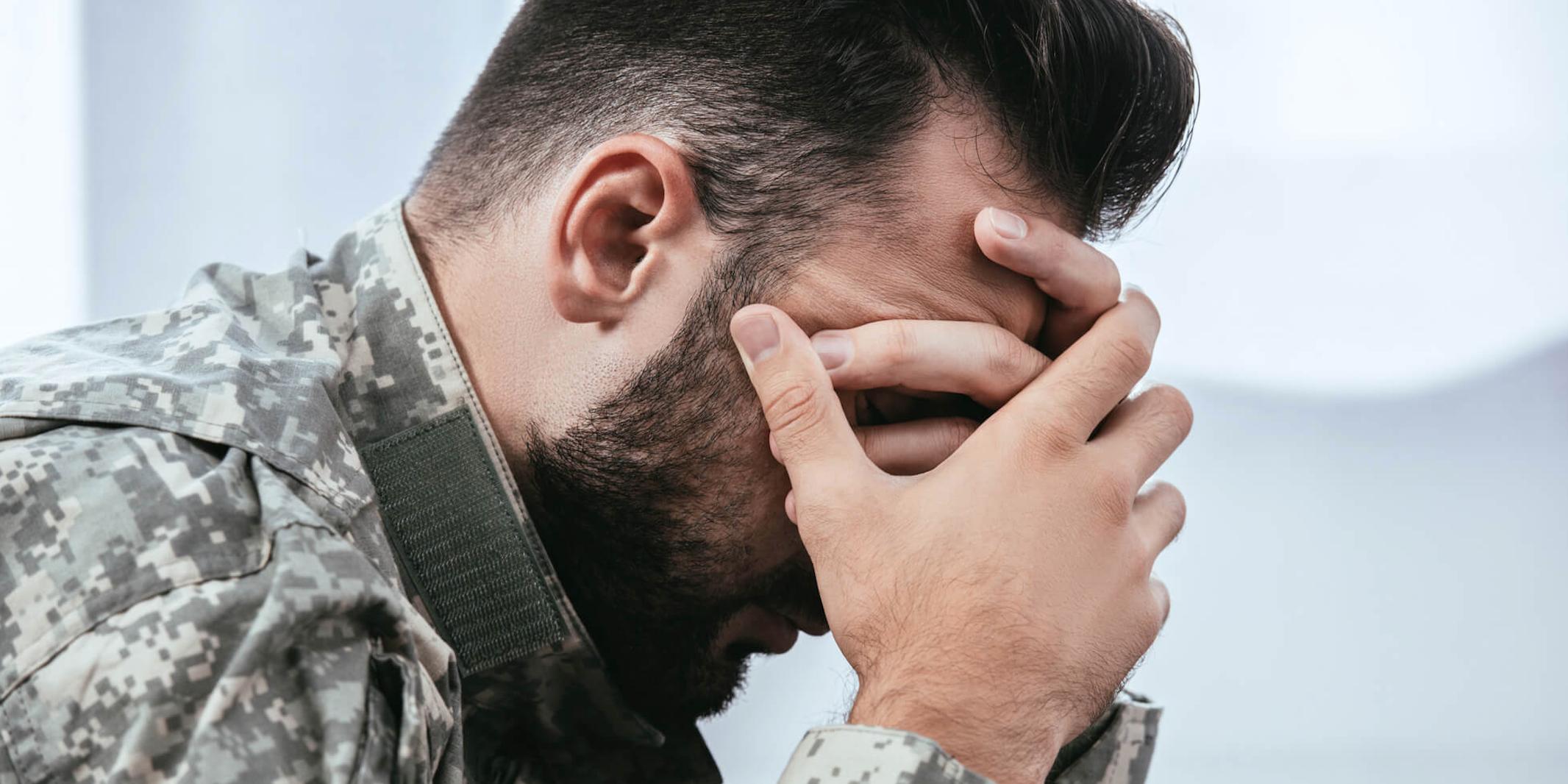 Depressed man in army uniform.