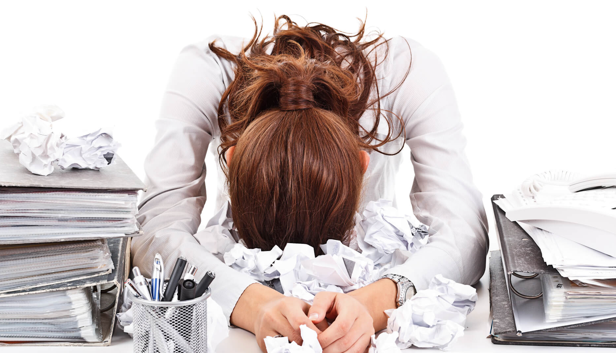 Stressed woman at her cluttered desk at her office